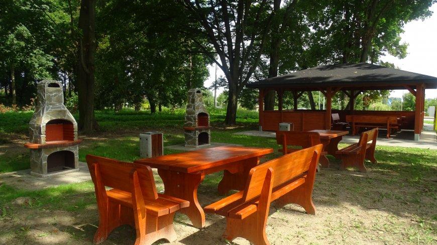 Zdjęcie przedstawiające miejsce rekreacyjne powstałe przy Orliku. (ławki, stoły, grille i altanę)