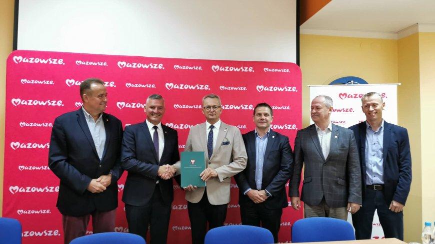 Wicemarszałek Rafał Rajkowski (drugi od prawej) przekazuje podpisaną umowę na dofinansowanie burmistrzowi Zwolenia Arkadiuszowi Sulimie.